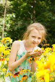 Attractive little girl standing in yellow flowers — Stock Photo