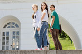 Three young people posing on a wall — Stock Photo