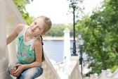 Pretty little girl posing on an outdoor staircase — Stock Photo