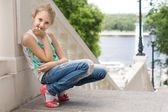 Cute young girl sitting on an outdoor staircase — Stock Photo