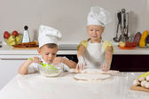Young children baking homemade pizzas — Stock Photo