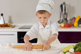 Little boy rolling out dough in the kitchen — Stock Photo