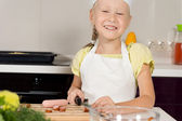 Smiling little girl preparing a meal — Stock Photo