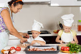 Mother teaching her children to cook — Stock Photo