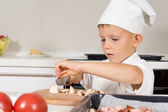 Cute little boy in a chefs toque slicing mushrooms — Stock Photo