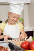 Happy little girl in a cooks uniform — Stock Photo
