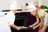 Two proud young children putting pizza in the oven — Foto de Stock