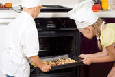 Young chefs placing their pizzas in the oven — Stock Photo