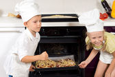 Happy children putting their pizzas in the oven — Stock Photo