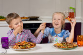 Two children celebrating eating their pizza — Stock Photo