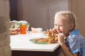 Hungry pretty little girl devouring homemade pizza — Stock Photo