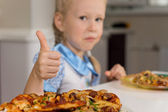 Small girl enjoying a plate of homemade pizza — Stock Photo