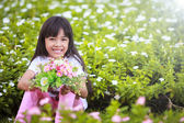 Asian little girl with flower in field of flowers — Stock Photo