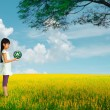 Little girl holding earth with recycle symbol at flower field — Stock Photo #19199191