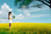 Little girl holding earth with recycle symbol at flower field — Stock Photo