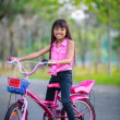 Asian little girl on bicycle in the park — Stock Photo