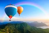 Kleurrijke warme lucht ballonnen vliegen over de berg — Stockfoto