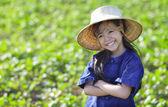 Lilla leende flicka bonde på gröna fält — Stockfoto