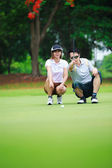Professional teaching young woman golfer — Stock Photo