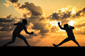 Silhouette fencers with sunset — Stock Photo