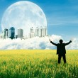 Businessman standing on the field and watching the future city o — Stock Photo
