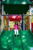 Smiling asian little girl sitting slide — Foto de Stock