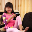 Asian little girl playing with tablet at home lying on sofa — Stock Photo