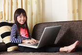 Asiatische mädchen mit computer zu hause — Stockfoto