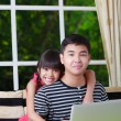 Little asian girl pointing on laptop with big brother — Stock Photo