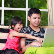Little asian girl pointing on laptop with big brother — Stockfoto