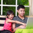 Little asian girl pointing on laptop with big brother - Стоковая фотография