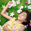 Little asian girl laying in green grass — Stock Photo