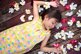Little asian girl laying on the floor with petals on hair — Stock Photo