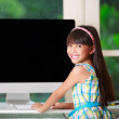 Little asian girl with computer at home — Stock Photo