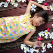 Little asian girl laying on the floor with petals on hair — Stock Photo #25967363