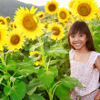 Closeup smiling girl in the sunflowers field — Stock Photo #26005693