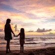 Mother and kid silhouettes on sunset beach — Stock Photo