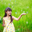 Portrait of little girl enjoy with soap bubbles on green meadow — Stock Photo #26596821