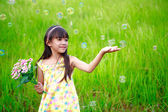 Portrait of little girl enjoy with soap bubbles on green meadow — Stock Photo