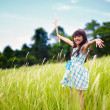 Little asian girl with open arms against green meadow — Stock Photo #26636447