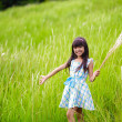 Little asian girl with open arms against green meadow — Stock Photo