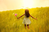 Little girl running on meadow with sunset — Stok fotoğraf