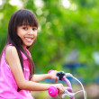 Little asian girl in a bicycle — Stock Photo
