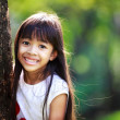 Cute little girl smiling in a park close up — Stock Photo