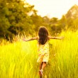 Stock Photo: Little girl running on meadow with sunset