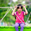 Crying little asian girl sitting alone on a playground — Stock Photo #27838083