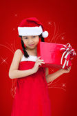 Little miss santa is happy about a gift — Stock Photo