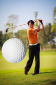 A golf ball just coming off the tee from a golfer in swing — Stock Photo