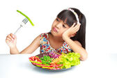 Little asian girl with expression of disgust against broccoli — Stock Photo