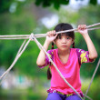 Sad little asian girl sitting alone on a playground — Stock Photo